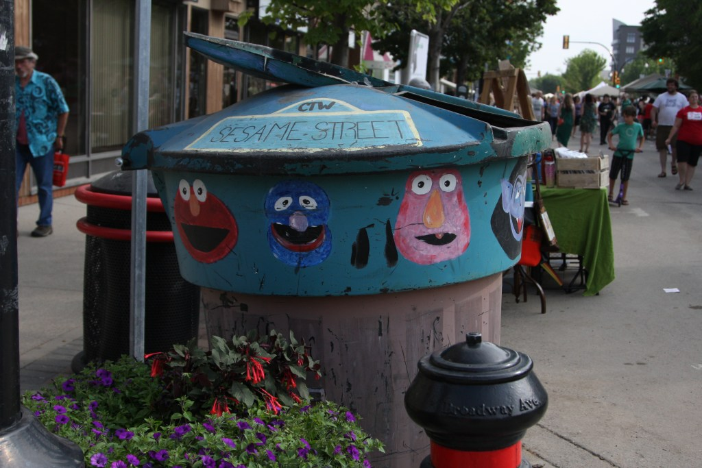 Sesame Street art covering a garbage can on the street in Saskatoon