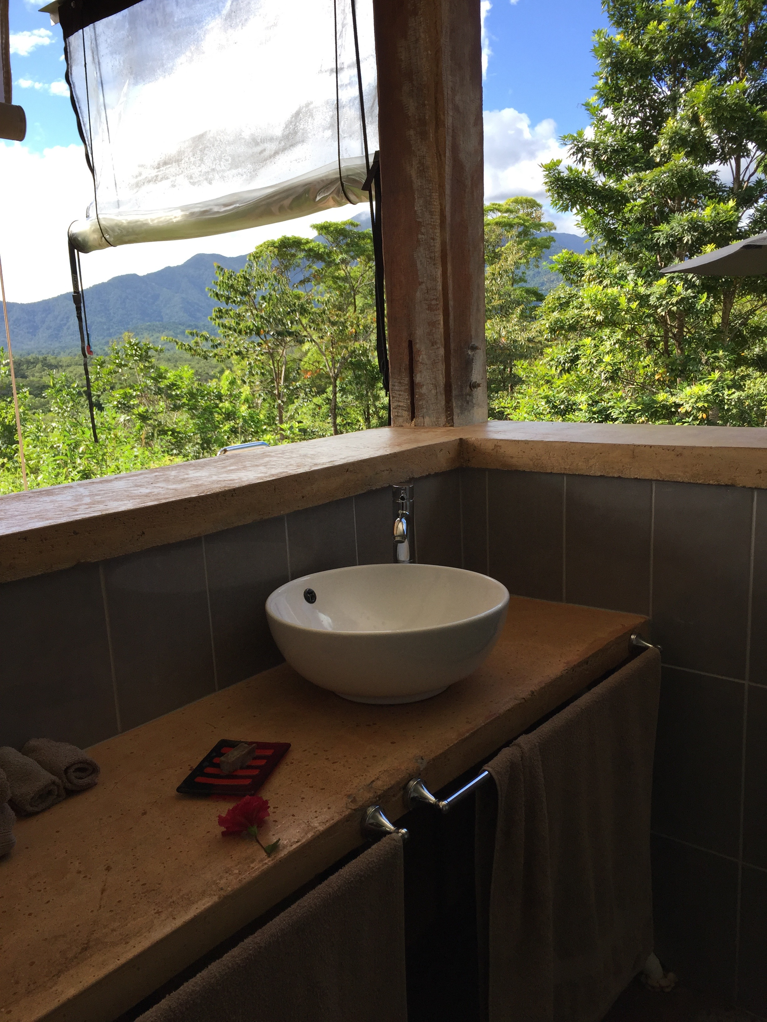 Bathroom corner counter and sink with glassless windows giving a view of the Daintree Rainforest in an Airbnb rental
