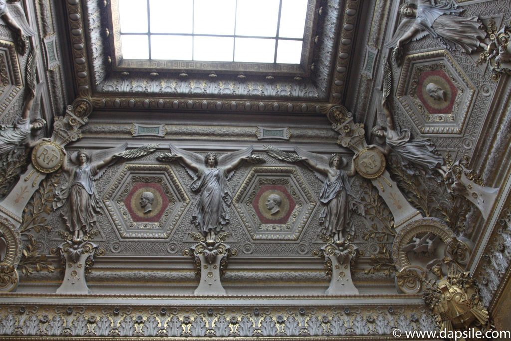 A Decorative Ceiling with a Window in the Louvre in Paris