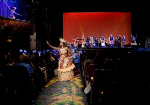 """HOLLYWOOD, CA - NOVEMBER 14: Musicians Olivia Foa'i, Opetaia Foa'i and band Te Vaka perform onstage (background) with dancers at The World Premiere of Disney's """"MOANA"""" at the El Capitan Theatre on Monday, November 14, 2016 in Hollywood, CA. (Photo by Jesse Grant/Getty Images for Disney) *** Local Caption *** Olivia Foa'i; Opetaia Foa'i"""