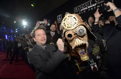 """HOLLYWOOD, CA - DECEMBER 10: Director Gareth Edwards (L) signs Christopher """"Dude Vader"""" Canole's helmet at The World Premiere of Lucasfilm's highly anticipated, first-ever, standalone Star Wars adventure, """"Rogue One: A Star Wars Story"""" at the Pantages Theatre on D"""