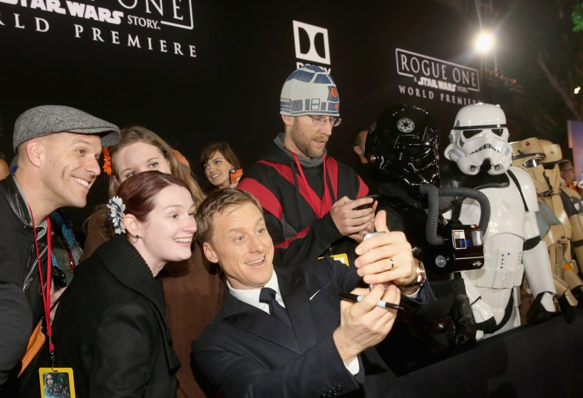 """HOLLYWOOD, CA - DECEMBER 10: Actor Alan Tudyk (C) takes a selfie with fans at The World Premiere of Lucasfilm's highly anticipated, first-ever, standalone Star Wars adventure, """"Rogue One: A Star Wars Story"""" at the Pantages Theatre on December 10, 2016 in Hollywood, California. (Photo by Jesse Grant/Getty Images for Disney) *** Local Caption *** Alan Tudyk"""