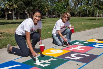 DISNEY VOLUNTEARS HELP BUILD PLAYGROUND IN ANAHEIM - Disney Ambassador Alexa Garcia, left, and Disney Alumni Maryann Meirowsky paint a new hop scotch court at Willow Park in Anaheim in Saturday, September 23, 2017. The park was transformed into a kid-designed play space in less than eight hours with the help of close to 300 volunteers from the City of Anaheim, Anaheim Family YMCA, Disney, Disney alumni, area residents and organizers from KaBOOM!. With this new addition to the neighborhood, 400 kids now have more opportunities to get the balanced and active play they need to thrive. Willow Park marks the ninth Disney-sponsored KaBOOM! playground in the city of Anaheim. (Joshua Sudock/Disney Parks)