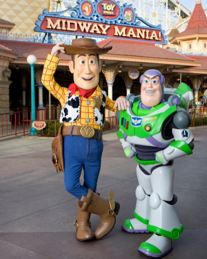 """HOWDY, PARTNER: Woody and Buzz Lightyear -- characters from the Disney-Pixar animated films """"Toy Story"""" and """"Toy Story 2"""" -- pose in front of """"Toy Story Mania!"""" at Disney's California Adventure at the Disneyland Resort in Anaheim, Calif. """"Toy Story Mania!"""" is a cutting-edge ride-through attraction that combines the fun of a video game with 4-D technology and interaction with favorite Disney-Pixar stars. Donning 3-D glasses and manning a """"spring-action shooter,"""" guests aim at playful targets along a colorful midway-themed route. Scores are tallied at the end of the attraction to determine the master of the midway. (Paul Hiffmeyer/Disneyland)"""