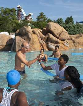 """Swim instructors team up with three-time Olympic gold medalist swimmer Rowdy Gaines to teach kids about water safety as part of the """"World's Largest Swimming Lesson"""" event at Disney's Blizzard Beach. Nearly 200 people participated at Disney as part of the global event that took place in 28 countries around the world. (David Roark, photographer)"""