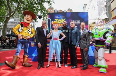 """LONDON, ENGLAND - JUNE 16: (L-R) Woody, Mark Nielsen, Bo Peep, Josh Cooley, Tom Hanks, Jonas Rivera and Buzz Lightyear attend the European premiere of Disney and Pixar's """"Toy Story 4"""" at the Odeon Luxe Leicester Square on June 16, 2019 in London, England. (Photo by Gareth Cattermole/Getty Images for Disney and Pixar)"""