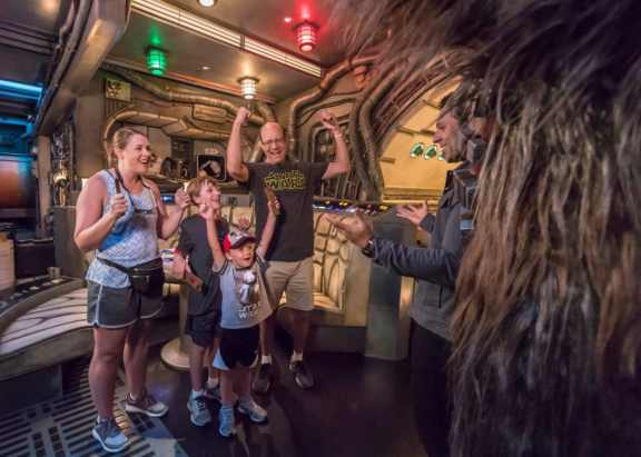 Eight-year-old Jonathan Ridgeway of Ocean Springs, Mississippi (back, center) becomes the 1 millionth guest to take to take the controls of Millennium Falcon: Smugglers Run at Star Wars: Galaxy's Edge at Disneyland Resort in Anaheim, Calif., Tuesday, July 16, 2019. The family (back to front) Becky Ridgeway, Jonathan Ridgeway (8); Roger Ridgeway and, Logan Ridgeway (4), was welcomed in the Main Hold of Millennium Falcon with a surprise visit from Chewbacca, followed by the ride experience and toasting blue and green milk with his family. This significant milestone comes just weeks since the land opened. (Joshua Sudock/Disneyland Resort)