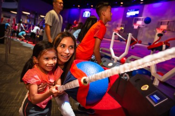 Guests at NBA Experience race against the clock at Slingshot to make as many baskets as possible using an oversized slingshot before time runs out. NBA Experience immerses guests of all ages and skills into the world of professional basketball as both a fan and player at Disney Springs at Walt Disney World Resort in Lake Buena Vista, Fla. (Steven Diaz, photographer)