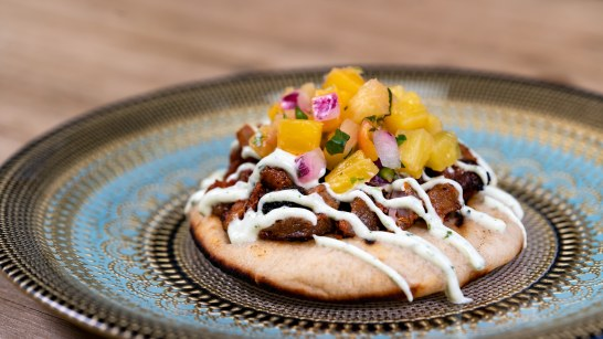 The Pork Al Pastor Naan Taco with pineapple pico de gallo and cilantro-lime Oikos Greek yogurt crema is part of the delicious food offerings during Disney Festival of Holidays. Available November 8 - January 6, this item can be be purchased at Merry Mashups marketplace in Disney California Adventure. (Disneyland Resort)