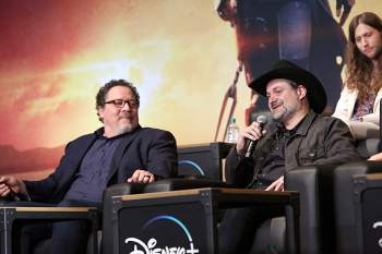 "HOLLYWOOD, CALIFORNIA - NOVEMBER 13: (L-R) Executive Producer Jon Favreau and Executive Producer/Director Dave Filoni speak onstage at the premiere of Lucasfilm's first-ever, live-action series, ""The Mandalorian,"" at the El Capitan Theatre in Hollywood, Calif. on November 13, 2019. ""The Mandalorian"" streams exclusively on Disney+. (Photo by Jesse Grant/Getty Images for Disney)"