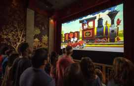"""Guests watch a new """"Mickey Mouse"""" cartoon short, """"Perfect Picnic,"""" to begin their Mickey & Minnie's Runaway Railway experience in Disney's Hollywood Studios at Walt Disney World Resort in Lake Buena Vista, Fla. The first ride-through attraction in Disney history featuring Mickey Mouse and Minnie Mouse brings guests into the vibrant world of """"Mickey Mouse"""" cartoon shorts. (Kent Phillips, photographer)"""