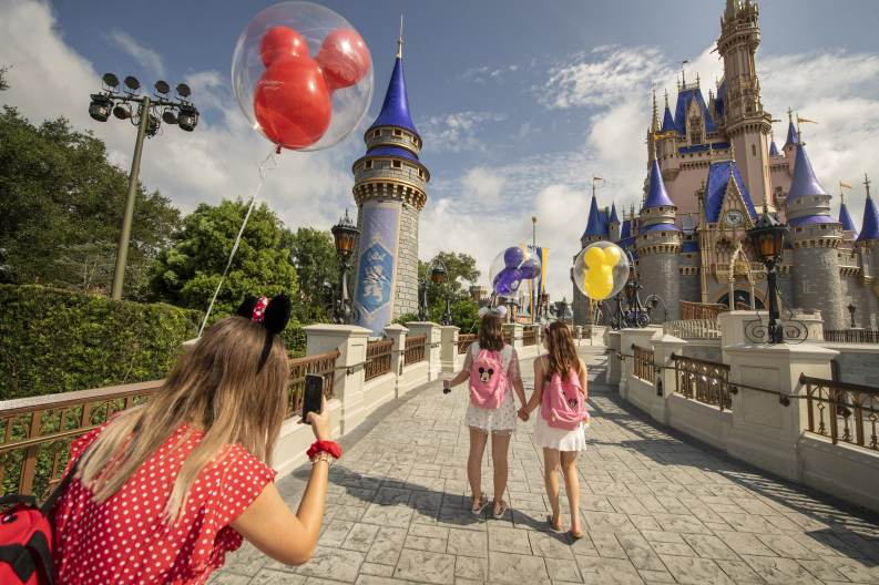 Guests stop to take a photo at Magic Kingdom Park, July 11, 2020, at Walt Disney World Resort in Lake Buena Vista, Fla., on the first day of the theme park's phased reopening. (Kent Phillips, Photographer)
