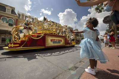 "Guests wave as the ""Mickey and Friends Cavalcade"" passes by on Main Street, U.S.A. at Magic Kingdom Park, July 11, 2020, at Walt Disney World Resort in Lake Buena Vista, Fla., on the first day of the theme park's phased reopening. (Kent Phillips, Photographer)"