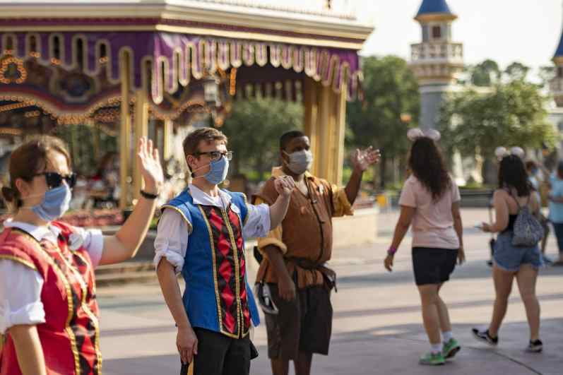 Disney cast members welcome guests to Magic Kingdom Park, July 11, 2020, at Walt Disney World Resort in Lake Buena Vista, Fla., on the first day of the theme park's phased reopening. (Matt Stroshane, Photographer)