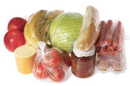 raw food isolated on white - apples, bananas, cheese, tomatoes, cabbage, bread, sausages, eggs, pot with peppers, all wrapped for purchase