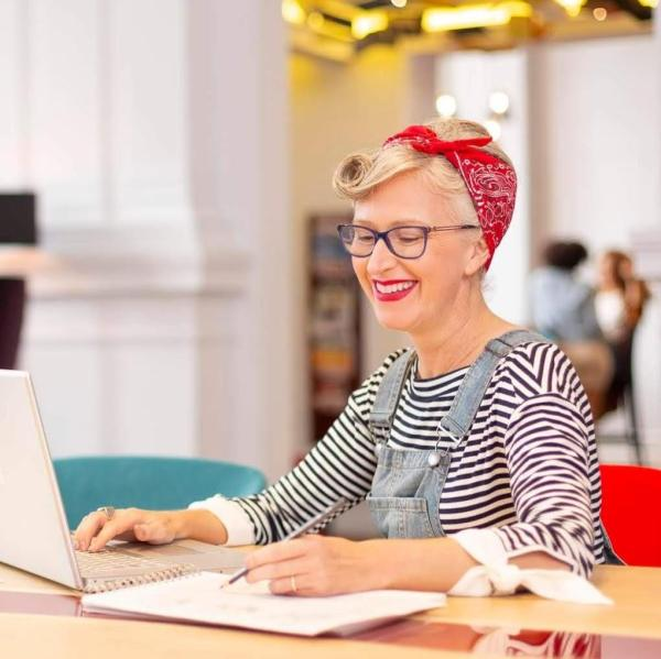Stylist Ghislaine Walker sitting at her desk wearing a striped t-shirt, denim dungarees and a red bandana  tied around her head
