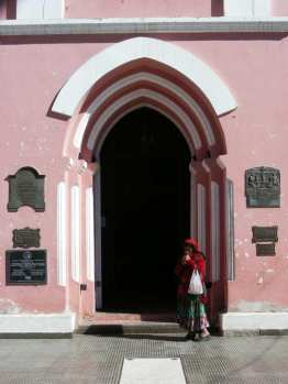 Tinogasta: local woman at the entrance to the main church