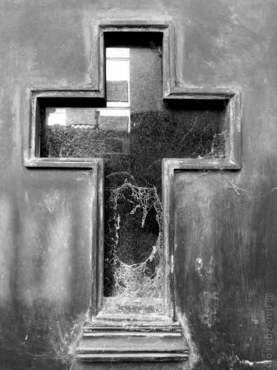 La Recoleta cemetery in Buenos Aires: cobwebs in a plain glass cross window in a door