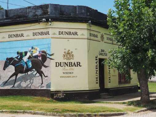 Corner bar in Villa 25 de Agosto with a mural showing a horse race