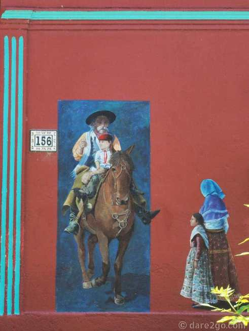 Dark red coloured house with murals depicting traditional gaucho scenes in 25 de Agosto - an old man holding a child and riding a horse