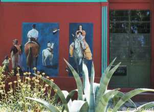 Dark red coloured house with murals depicting traditional gaucho scenes in 25 de Agosto - 2 pictures