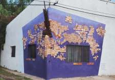 A three-dimensional piece of wall-art on a house in San Gregorio. Part of the ship's bow is covered with hand-made mosaic tiles.