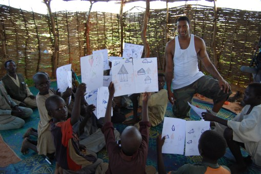 Tracy McGrady meeting with children in the camp. They are showing him drawings of how they remembered their homes being attacked. Photo: Darfur Dream Team