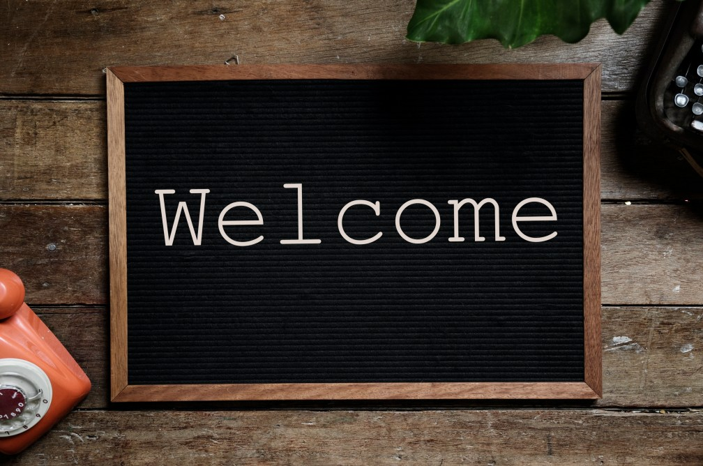 """A black board on a desk, showing the word """"Welcome""""."""