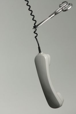 A corded telephone swinging upside-down with scissors cutting the cable
