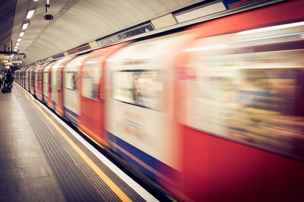 A blurred photo of a train passing through a subway station at speed.