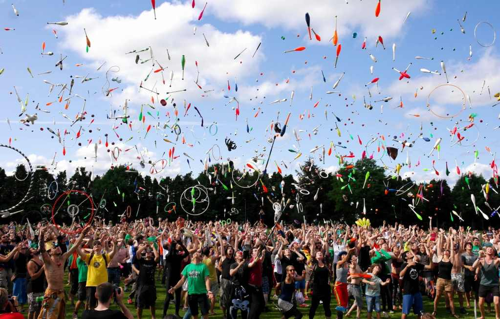 A large group of people throwing balls, juggling batons and hoops up in the air