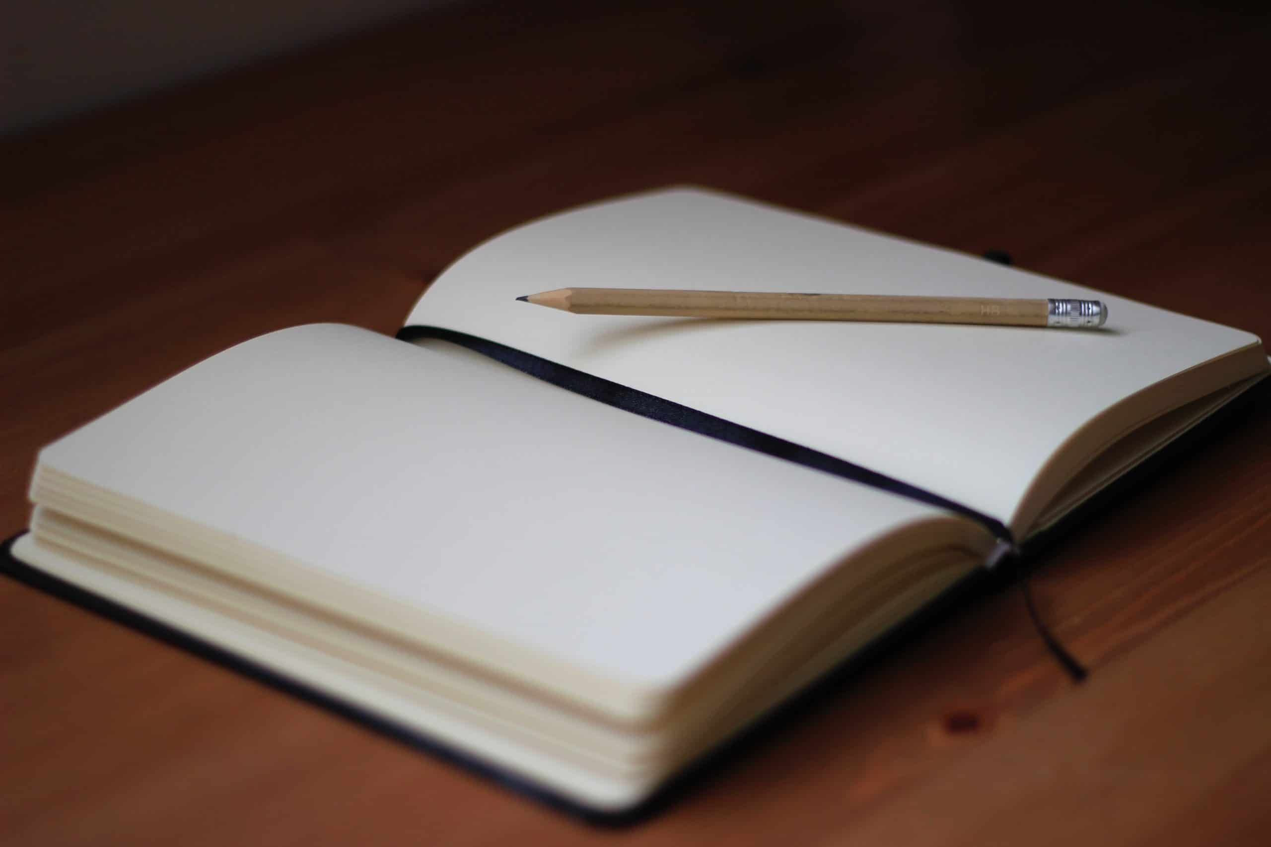 A picture of a notebook lying open on a blank page, with a pencil resting on the page
