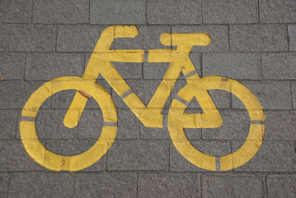 A painted bicycle sign on a grey paved road