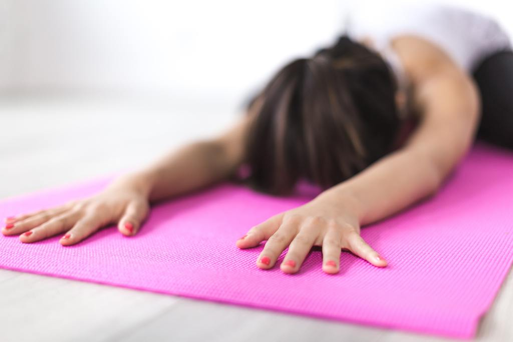 A woman kneeling on a pink yoga mat, stretching forward with her face near the ground