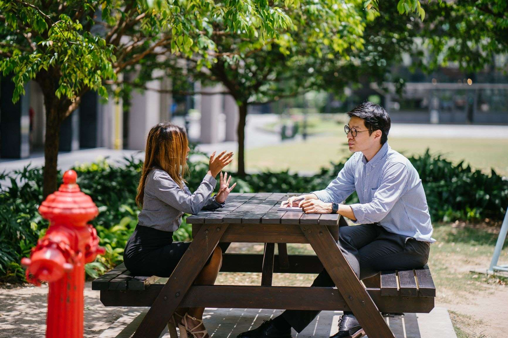 A woman and man sitting at an outdoor table, deep in conversation