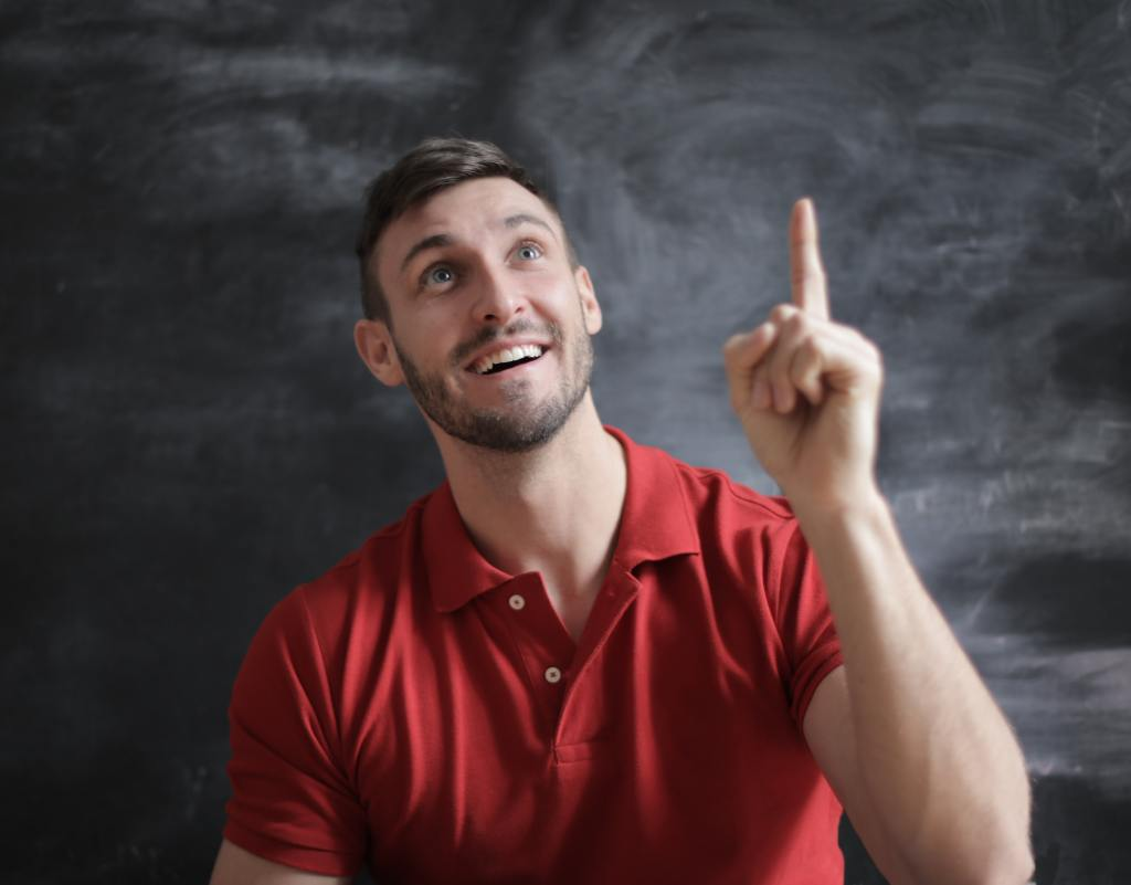 A man in a red shirt in front of a black background. He is holding his left arm in the air with the index finger raised, looking upward and smiling as though he has had an insight. Image credit: Pexels