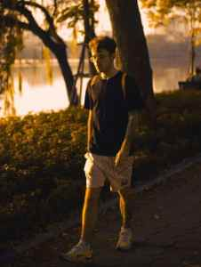 A man walking in a park at sunset, wearing earphones