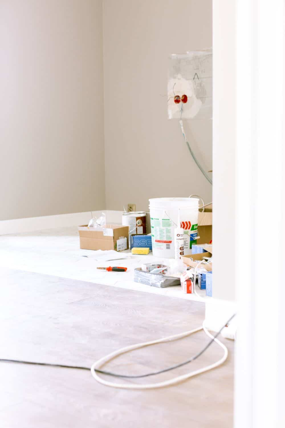 A picture of an empty room with all resources required to paint it on a sheet in the middle