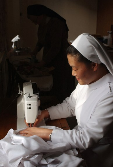 """Sister Helen Ahn sews a new habit for one of the sisters at the Immaculata Monastery. Sister Paula Leick irons habits in the background. SUMMARY: """"LIFE INSIDE THE IMMACULATA MONASTERY"""" """"So faith, hope, love remain, these three: but the greatest of these is love."""" -- 1st Corinthians 13:13. The 40 Benedictine sisters of the Immaculata Monastery in Norfolk live by that Bible verse. They start and end each day with prayer. These images are just a small glimpse into their lives."""