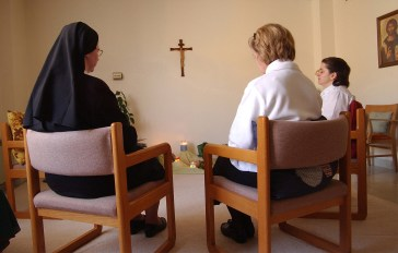 """Sister Celine Schock, left, and postulants Ann Dana and Chris Velilla, right, spend time in their prayer room reflecting on the Scriptures. SUMMARY: """"LIFE INSIDE THE IMMACULATA MONASTERY"""" """"So faith, hope, love remain, these three: but the greatest of these is love."""" -- 1st Corinthians 13:13. The 40 Benedictine sisters of the Immaculata Monastery in Norfolk live by that Bible verse. They start and end each day with prayer. These images are just a small glimpse into their lives."""