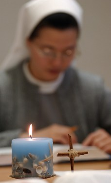 """A candle and cross rest on a table during discussion of the day's scripture reading at the monastery. The sisters like candles because they symbolize the light of Christ, the light of the world. SUMMARY: """"LIFE INSIDE THE IMMACULATA MONASTERY"""" """"So faith, hope, love remain, these three: but the greatest of these is love."""" -- 1st Corinthians 13:13. The 40 Benedictine sisters of the Immaculata Monastery in Norfolk live by that Bible verse. They start and end each day with prayer. These images are just a small glimpse into their lives."""
