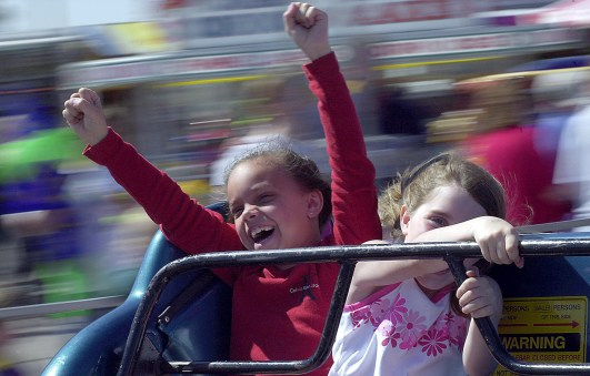 """Rachel Scheinost (left) and Lexi McCoy ride the """"Sizzler"""" at the D.C. Lynch carnival Sunday afternoon, May 19, 2002."""