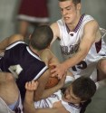 Norfolk's Kris Mather (right) and Josh Jorgensen (bottom right) tangle with Lincoln Northeast's Angelo Stabler (4) while trying to gain control of a loose ball during action Friday night, Jan. 18, 2002.
