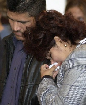 Tita Martinez cries as she leans on her husband, Ezequiel's, shoulder during a healing ceremony Friday night, Sept. 27, 2002. Five people were murdered in a botched bank robbery the previous day.
