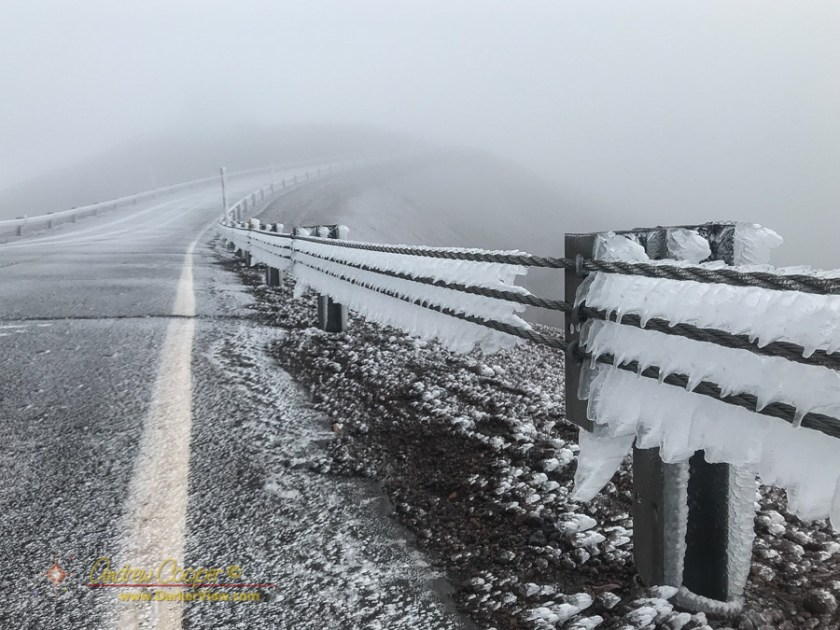 The cable safety guardrails covered in ice from freezing fog atop Mauna Kea