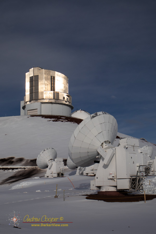 Several of the SMA antenna in front of the Subaru Telescope