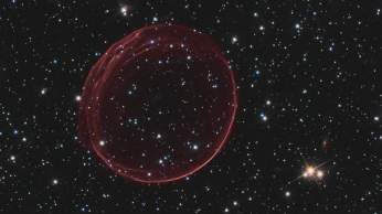 "A delicate sphere of gas, photographed by NASA's Hubble Space Telescope, floats serenely in the depths of space. The pristine shell, or bubble, is the result of gas that is being shocked by the expanding blast wave from a supernova. Called SNR 0509-67.5 (or SNR 0509 for short), the bubble is the visible remnant of a powerful stellar explosion in the Large Magellanic Cloud (LMC), a small galaxy about 160,000 light-years from Earth. Ripples in the shell's surface may be caused by either subtle variations in the density of the ambient interstellar gas, or possibly driven from the interior by pieces of the ejecta. The bubble-shaped shroud of gas is 23 light-years across and is expanding at more than 11 million miles per hour (5,000 kilometers per second). Astronomers have concluded that the explosion was one of an especially energetic and bright variety of supernovae. Known as Type Ia, such supernova events are thought to result from a white dwarf star in a binary system that robs its partner of material, takes on much more mass than it is able to handle, and eventually explodes. Hubble's Advanced Camera for Surveys observed the supernova remnant on Oct. 28, 2006, with a filter that isolates light from glowing hydrogen seen in the expanding shell. These observations were then combined with visible-light images of the surrounding star field that were imaged with Hubble's Wide Field Camera 3 on Nov. 4, 2010. With an age of about 400 years as seen from Earth, the supernova might have been visible to southern hemisphere observers around the year 1600. However, there are no known records of a ""new star"" in the direction of the LMC near that time. A more recent supernova in the LMC, SN 1987A, did catch the eye of Earth viewers and continues to be studied with ground- and space-based telescopes, including Hubble."