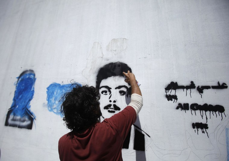 "Artist Murad Subai paints a picture of a disappeared political figure next to a defaced picture he previously painted, as part of ""The Walls Remember"" campaign he has launched to put focus on people who have disappeared in what is known as the ""forced disappearance,"" in Sanaa September 27, 2012. (Khaled Abdullah/Reuters)"