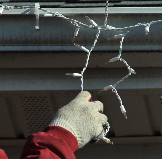 """Роберто Моралес из Фредерик, штат Мэриленд, компания """"Король Рождество"""", зависает строки сосулька фары, при оформлении Timonium дома.  (Gene Суини Jr. / Baltimore Sun)"""