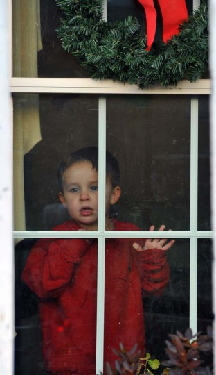 """3 year old son, Hayden, watches from his home as decorations are installed by the Frederick, Md, company """"The King of Christmas"""", on his Timonium home. (Gene Sweeney Jr./Baltimore Sun)"""